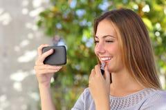 Mujer hermosa que compone usando un teléfono elegante como espejo Foto de archivo