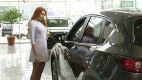 Mujer hermosa que comprueba hacia fuera un nuevo coche en el salón automotriz de la representación almacen de metraje de vídeo