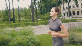 Mujer hermosa que corre en la sacudida de la mañana mientras que entrenamiento cardiio al aire libre almacen de metraje de vídeo