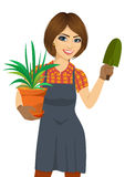 Mujer hermosa que cultiva un huerto que sostiene la planta verde de Chlorophytum en el pote y la paleta Fotos de archivo