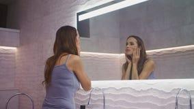 Mujer hermosa que da masajes a la cara en cuarto de baño Persona femenina atractiva que levanta su cara metrajes