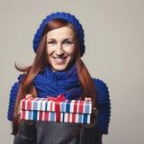 Mujer hermosa que da un regalo colorido de la Navidad Fotografía de archivo