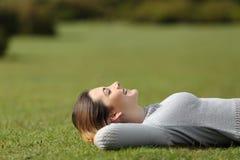 Mujer hermosa que descansa sobre la hierba en un parque Imagen de archivo libre de regalías