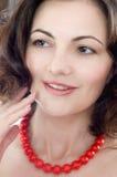 Mujer hermosa que desgasta granos rojos del corall Imagenes de archivo