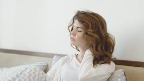 Mujer hermosa que despierta en cama por mañana Mujer enferma que da masajes al cuello almacen de video
