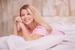 Mujer hermosa que despierta en la cama Imágenes de archivo libres de regalías