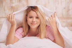 Mujer hermosa que despierta en la cama Fotos de archivo