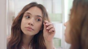Mujer hermosa que despluma las cejas con las pinzas en espejo en el cuarto de baño metrajes
