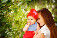 Mujer hermosa que detiene al bebé curioso lindo del niño Foto de archivo libre de regalías