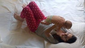 Mujer hermosa que detiene al bebé infantil sobre la cabeza Niño dulce en abrazo de la momia almacen de video