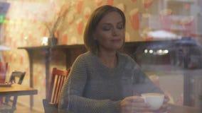 Mujer hermosa que disfruta de la bebida caliente, soñando sobre futuro y haciendo planes almacen de metraje de vídeo