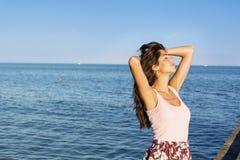 Mujer hermosa que disfruta de la puesta del sol del verano en la playa Imagen de archivo