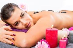 Mujer hermosa que disfruta de un masaje de piedra caliente imagen de archivo libre de regalías
