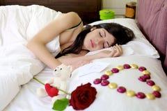 Mujer hermosa que duerme con el regalo de las tarjetas del día de San Valentín Fotografía de archivo