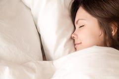 Mujer hermosa que duerme en la cama acogedora, opinión superior del headshot del primer Imágenes de archivo libres de regalías