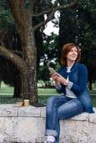 Mujer hermosa que envía un mensaje en su teléfono en el parque Imagenes de archivo