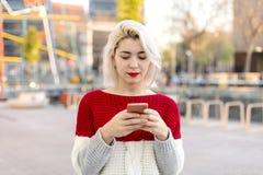 Mujer hermosa que escribe un mensaje en su teléfono Imágenes de archivo libres de regalías