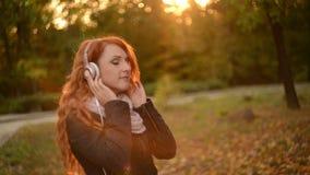 Mujer hermosa que escucha la música en los auriculares almacen de metraje de vídeo