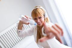 Mujer hermosa que escucha la música y que canta con la botella de agua en casa Fotos de archivo libres de regalías