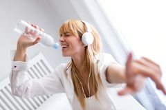 Mujer hermosa que escucha la música y que canta con la botella de agua en casa Fotos de archivo