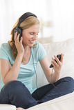 Mujer hermosa que escucha la música a través de los auriculares Foto de archivo libre de regalías