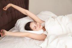 Mujer hermosa que estira con placer en cama Imagen de archivo libre de regalías