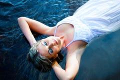 Mujer hermosa que flota en el río azul Foto de archivo