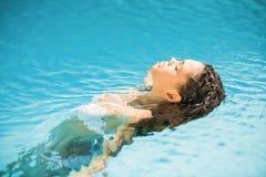 Mujer hermosa que flota en piscina Foto de archivo libre de regalías