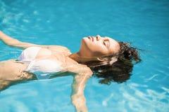 Mujer hermosa que flota en piscina Imagen de archivo
