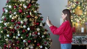Mujer hermosa que fotografía en el árbol de navidad del smartphone en casa metrajes
