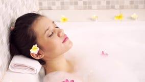 Mujer hermosa que goza del balneario en bañera almacen de metraje de vídeo