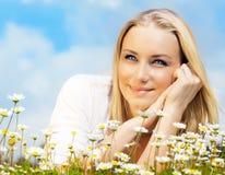 Mujer hermosa que goza del campo de la margarita y del cielo azul Foto de archivo