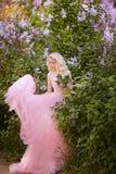 Mujer hermosa que goza del jardín de la lila, mujer joven con las flores en parque verde el caminar alegre del adolescente al air Imagen de archivo libre de regalías