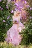 Mujer hermosa que goza del jardín de la lila, mujer joven con las flores en parque verde el caminar alegre del adolescente al air Foto de archivo libre de regalías