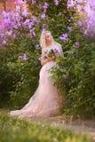 Mujer hermosa que goza del jardín de la lila, mujer joven con las flores en parque verde el caminar alegre del adolescente al air Imagenes de archivo
