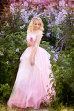Mujer hermosa que goza del jardín de la lila, mujer joven con las flores en parque verde el caminar alegre del adolescente al air Fotos de archivo libres de regalías