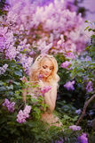 Mujer hermosa que goza del jardín de la lila, mujer joven con las flores en parque verde el caminar alegre del adolescente al air Foto de archivo
