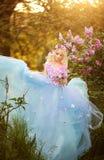 Mujer hermosa que goza del jardín de la lila, mujer joven con las flores en parque verde el caminar alegre del adolescente al air Fotos de archivo