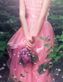 Mujer hermosa que goza del jardín de la lila, mujer joven con las flores en parque verde el caminar alegre del adolescente al air Fotografía de archivo