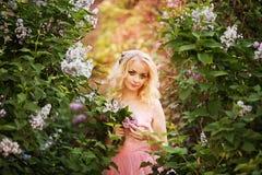 Mujer hermosa que goza del jardín de la lila, mujer joven con las flores en parque verde el caminar alegre del adolescente al air Imagen de archivo
