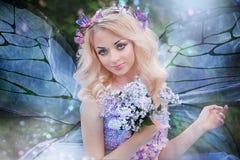 Mujer hermosa que goza del jardín de la lila, mujer joven con las flores en parque verde el caminar alegre del adolescente al air Imágenes de archivo libres de regalías
