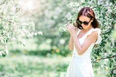 Mujer hermosa que goza del olor en jardín de la cereza de la primavera foto de archivo libre de regalías