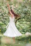 Mujer hermosa que goza del olor en jardín de la cereza de la primavera imagen de archivo