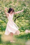Mujer hermosa que goza del olor en jard?n de la cereza de la primavera foto de archivo
