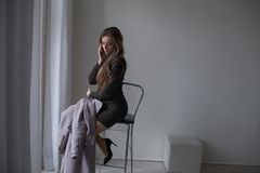 Mujer hermosa que habla en el teléfono en la ventana Imagen de archivo libre de regalías