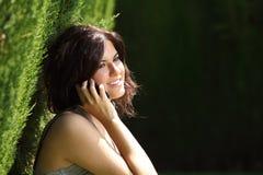 Mujer hermosa que habla en el teléfono móvil en un parque Fotos de archivo libres de regalías
