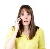 Mujer hermosa que habla en el teléfono móvil y que está en el choque de las noticias Fotos de archivo