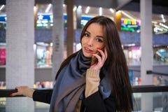 Mujer hermosa que habla en el teléfono mientras que sale en un día de compras imagen de archivo libre de regalías