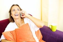 Mujer hermosa que habla en el teléfono que sonríe en casa Imágenes de archivo libres de regalías