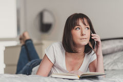 Mujer hermosa que habla en smartphone en su dormitorio Fotos de archivo libres de regalías